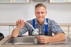 Young Male Plumber Fixing Faucet In Sink Of Kitchen - stock photo