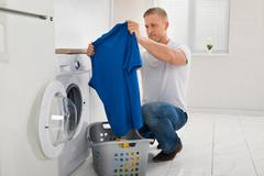 Young Man Looking At T-shirt While Using Washing Machine Appliance In Kitchen Stock Photos