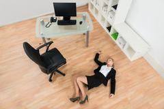 High Angle View Of Young Businesswoman Fainted On Floor In Office - stock photo