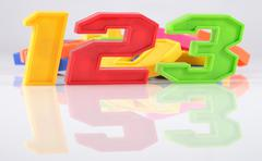 Colorful plastic numbers 123 with reflection on white - stock photo