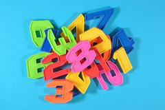 Colorful plastic numbers on a blue background - stock photo