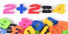 Colorful plastic numbers. Mathematics example two plus two is four Stock Photos
