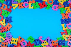 Frame of plastic colorful alphabet letters on a blue Stock Photos