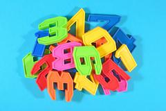Heap of plastic colored numbers on a blue background close up - stock photo