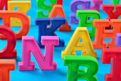 Plastic colorful alphabet letters close up on a blue - stock photo