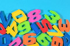 Plastic colored numbers on a blue background Stock Photos