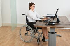 Happy Businesswoman Sitting On Wheelchair While Working On Computer At Desk Kuvituskuvat