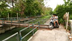 Young Thai couple ride motorbike over small steel bridge crossing green canal Stock Footage