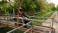 Vacant motorcycle taxi drive through steel gangway, narrow bridge at rural place Stock Footage