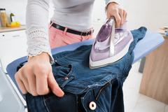 Close-up Of Woman Ironing Jeans On Ironing Board Stock Photos