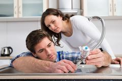 Young Woman Looking At Plumber Fixing Steel Tap In Kitchen Sink Stock Photos