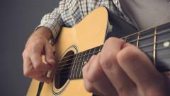 Hand picking strings on acoustic guitar - stock footage