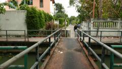 POV camera cross small pedestrian bridge, walk at suburban area of Bangkok Stock Footage
