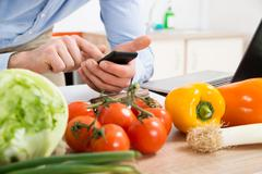 Close-up Of Person Hands Using Mobile Phone At The Worktop With Vegetables In Stock Photos