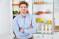 Portrait Of Handsome Man With Armcrossed Standing In Front Of Open Fridge - stock photo