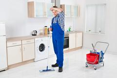 Stock Photo of Young Male Worker Cleaning Floor With Mop In House