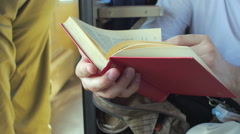 Man reads red book in a train with passengers. Stock Footage