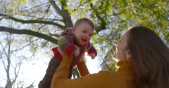 Mother lifting up her 8m old baby, fall-time - stock footage