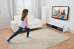 Girl Doing Exercise While Watching Program On Television At Home Kuvituskuvat