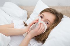 Sick Girl On Bed Sneezing In Handkerchief In Bedroom - stock photo