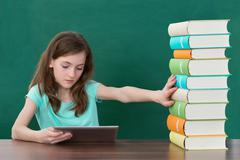 Girl Using Digital Tablet And Avoiding Stack Of Books At Desk In Classroom Stock Photos