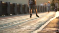 Unrecognizable people are skating and biking at sunset - stock footage