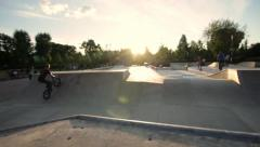Skateboard park with BMX bike rider and skateboarders. Dolly shot Stock Footage