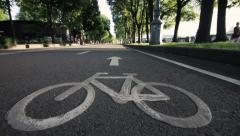 Path with sign for bicyclists in the park. Dolly shot. Stock Footage