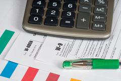tax reporting forms with green pen and calculator - stock photo