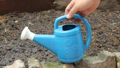 Man Hand holding Blue watering can on vegetable garden Stock Footage