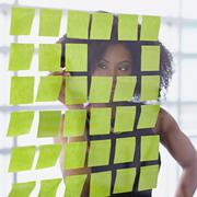 Portrait of a business woman with an afro behind sticky notes in bright glass Stock Photos