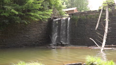 Waterfall beneath a house on a sunny day in Woodstock Stock Footage