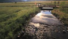 Aerial flying over magical stream river and crossing bridge Stock Footage
