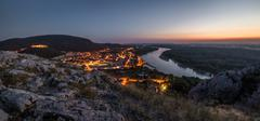 View of Lit Small City with River from the Hill at Sunset - stock photo