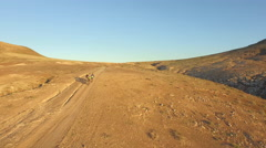 AERIAL: Flying over extreme bikers bicycling through the desert valley Stock Footage
