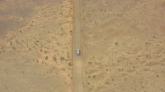AERIAL: Flying above the car driving through huge sandy desert Stock Footage