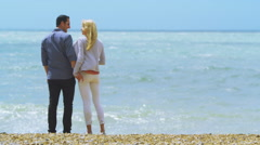 4K Attractive romantic couple kiss at the beach as they look out to sea Stock Footage