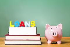 Student loan theme with textbooks and piggy bank - stock photo