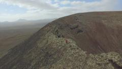 Stock Video Footage of AERIAL: Young woman hiking on the edge of volcano crater