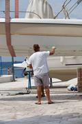 Man painting a boat - stock photo