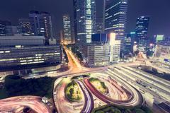 Spinning illuminated traffic loops outside the entrance of Shinjuku Station,  Stock Photos