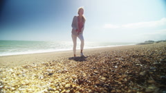 Beautiful woman walking alone on the beach on a sunny day Stock Footage