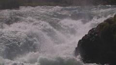 WHITE WATER RAPIDS CRASHING AGAINST RIVER ROCK – PULL BACK ZOOM - stock footage