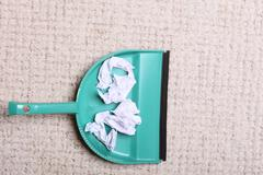 Stock Photo of Green dustpan for house work with garbage papers on floor indoors. Cleaning