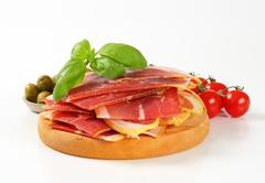 Sliced Prosciutto crudo on cutting board Stock Photos