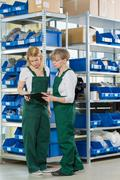 Women are checking availability of products in the warehouse - stock photo