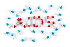 Red capsule and blue capsule in AIDS WORD Stock Photos