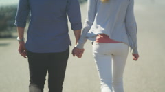 Attractive couple holding hands as they walk through seaside town.  Stock Footage