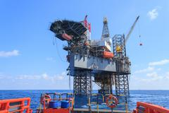 Offshore Jack Up Drilling Rig Over The Production Platform in The Middle of T - stock photo