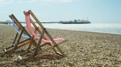 4K Colourful striped deckchairs on Brighton beach, UK. No people.  - stock footage